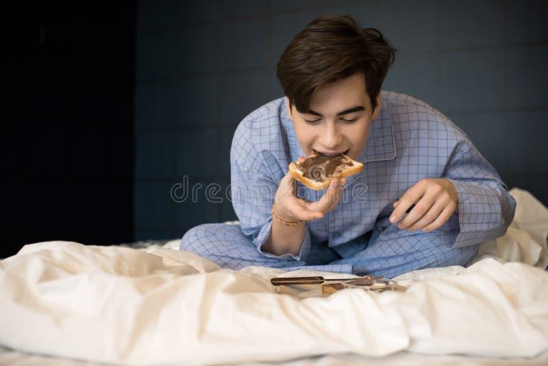 Menino que come o brinde crocante na cama fotos de stock royalty free