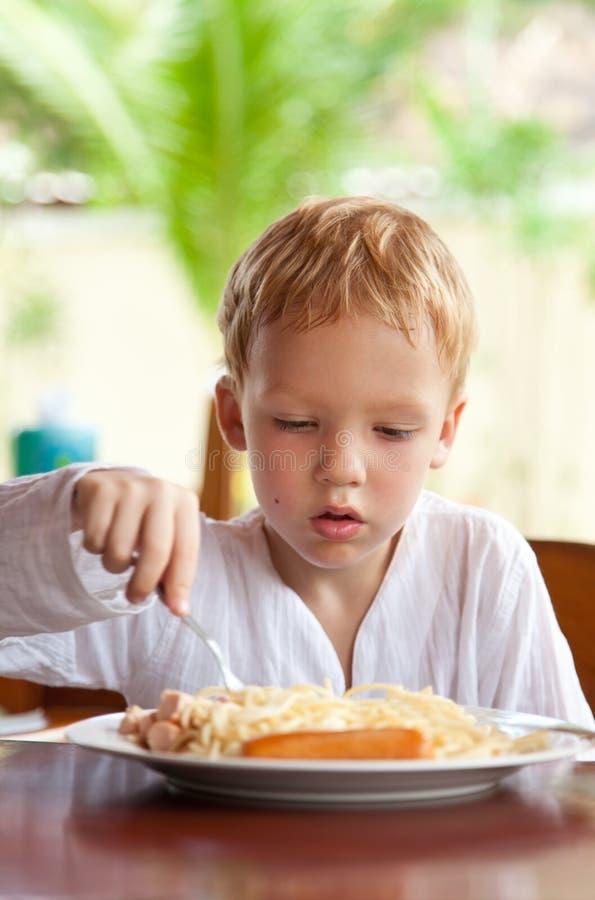 Menino que come o espaguete com salsichas ao ar livre imagens de stock