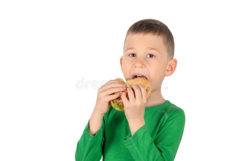 Menino que come o hamburguer foto de stock