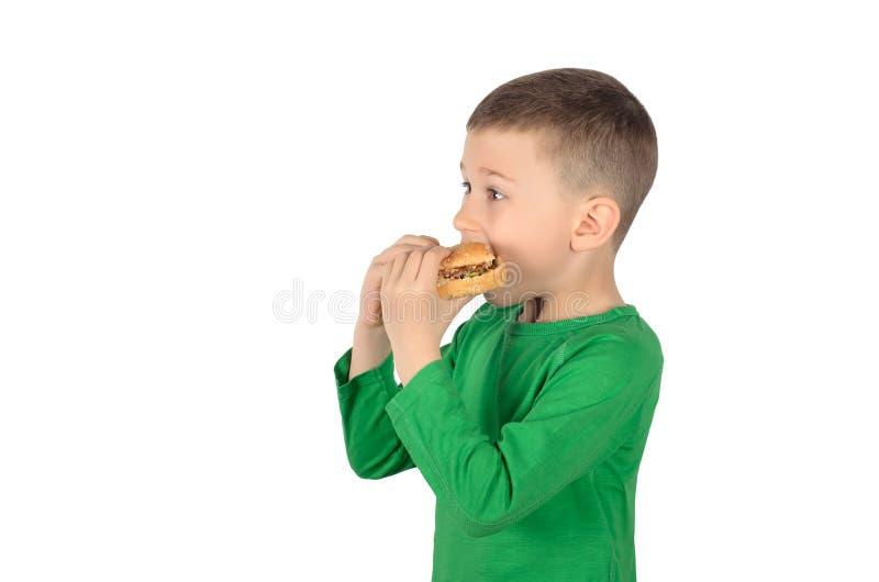 Menino que come o hamburguer imagem de stock