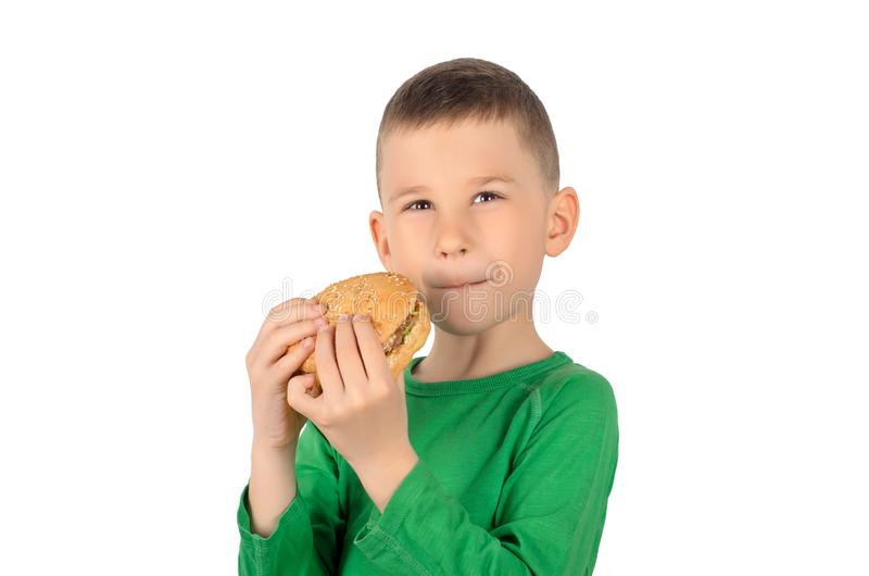Menino que come o hamburguer imagens de stock