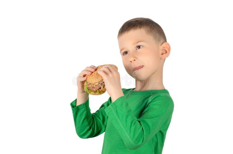 Menino que come o hamburguer foto de stock royalty free