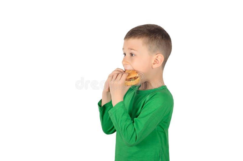 Menino que come o hamburguer imagem de stock royalty free