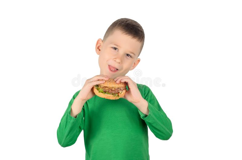 Menino que come o hamburguer fotos de stock royalty free