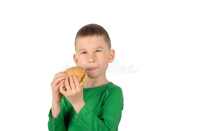 Menino que come o hamburguer fotografia de stock