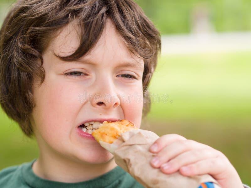 Menino que come o pão fotografia de stock