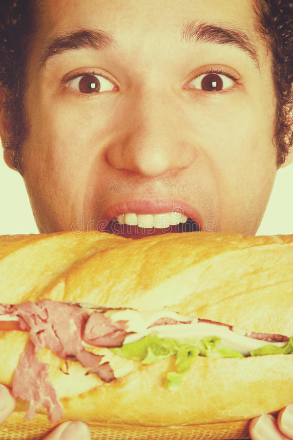 Menino que come o sanduíche foto de stock