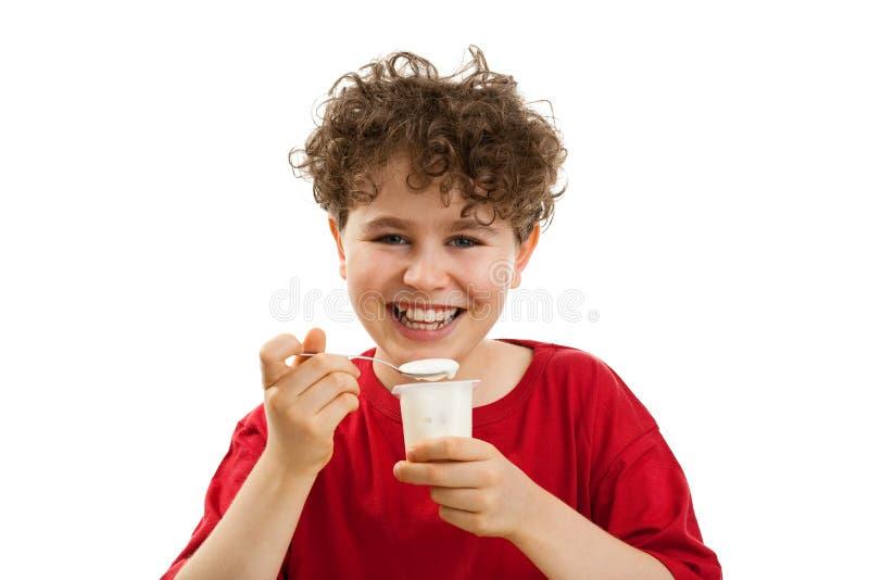 Menino que come o yogurt foto de stock