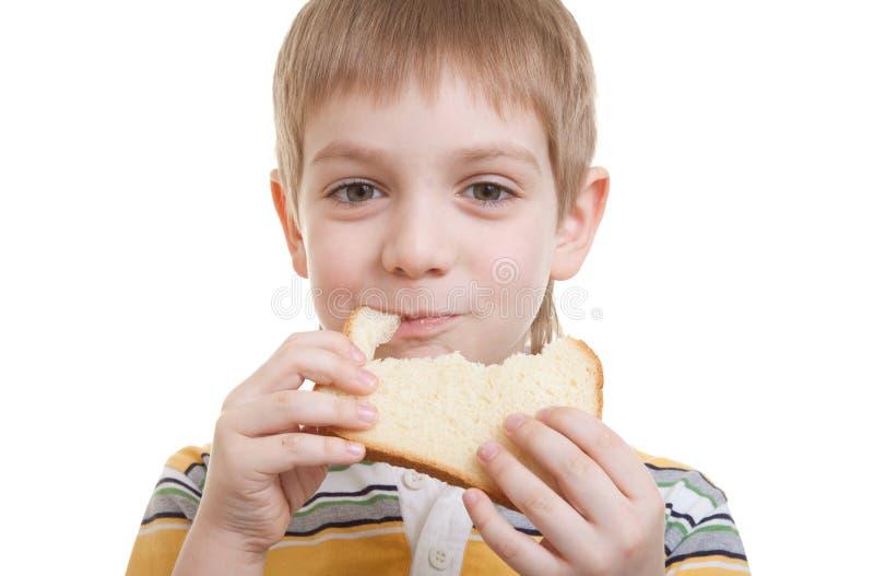 Menino que come a parte de pão imagem de stock royalty free