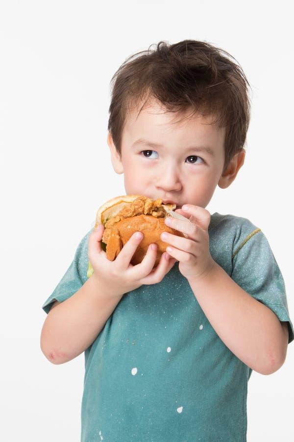 Menino que come um hamburguer fotografia de stock royalty free