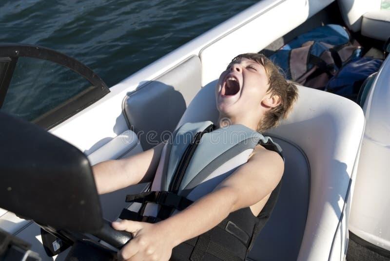 Menino que conduz o barco do esqui rapidamente imagens de stock royalty free