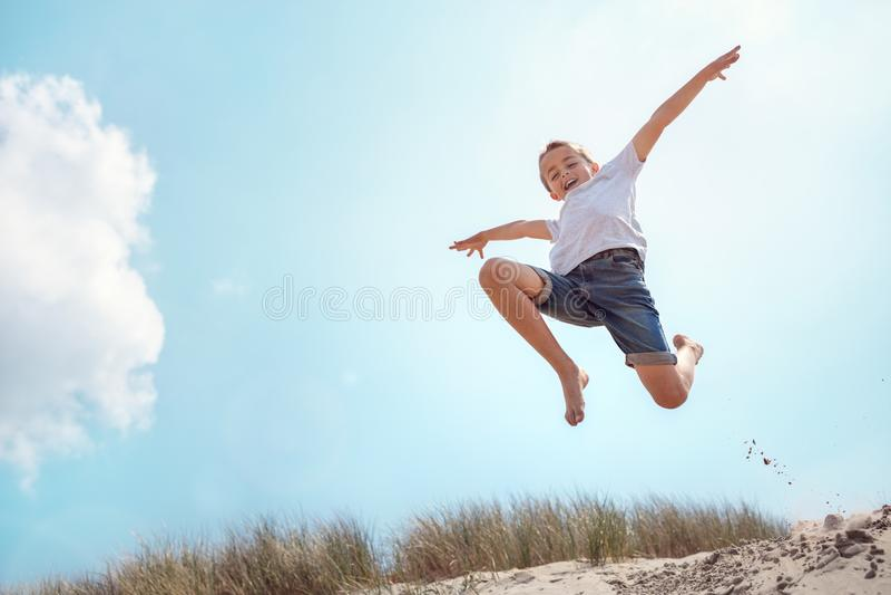 Menino que corre e que salta sobre a duna de areia em férias da praia foto de stock