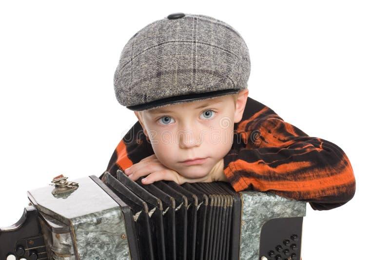 Menino que desgasta um tampão com acordeão. imagens de stock royalty free