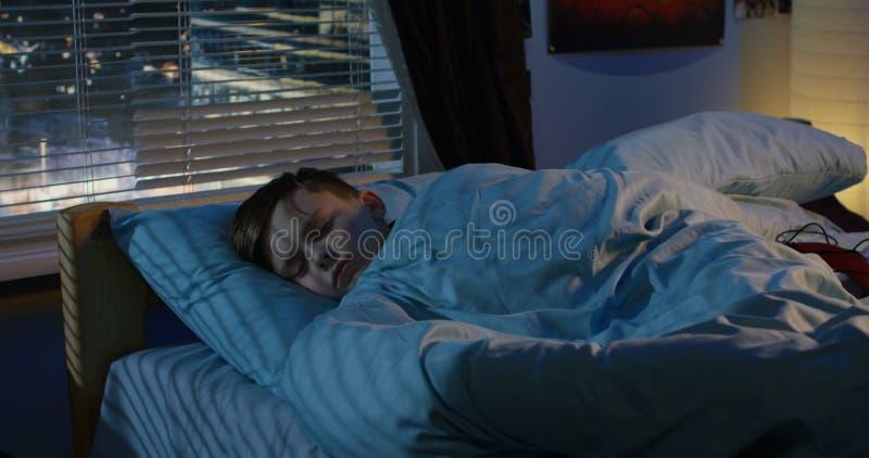 Menino que dorme em sua cama foto de stock royalty free