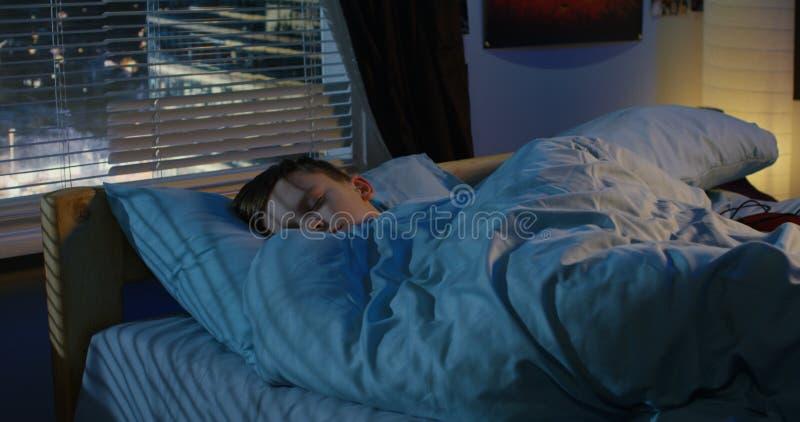 Menino que dorme em sua cama foto de stock