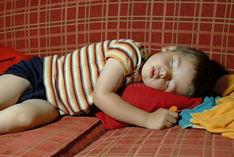 Menino que dorme em um sofá vermelho fotos de stock royalty free