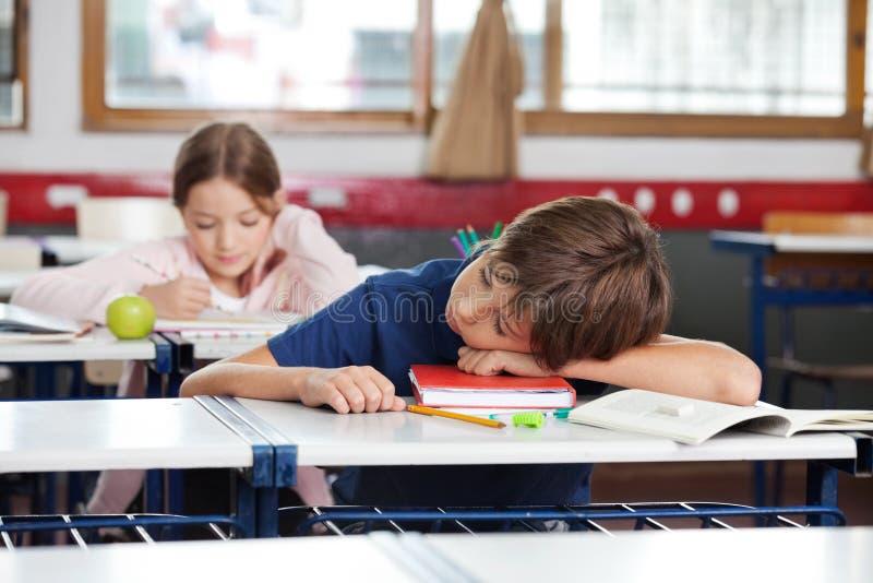 Menino que dorme na mesa na sala de aula fotos de stock