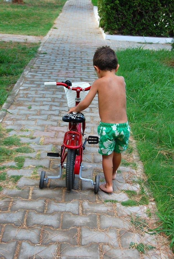 Menino que empurra a bicicleta fotos de stock