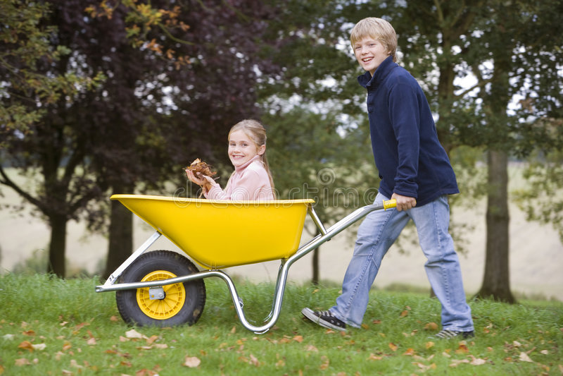 Menino que empurra a menina no wheelbarrow fotos de stock royalty free