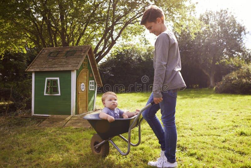 Menino que empurra o irmão In Garden Wheelbarrow do bebê fotografia de stock