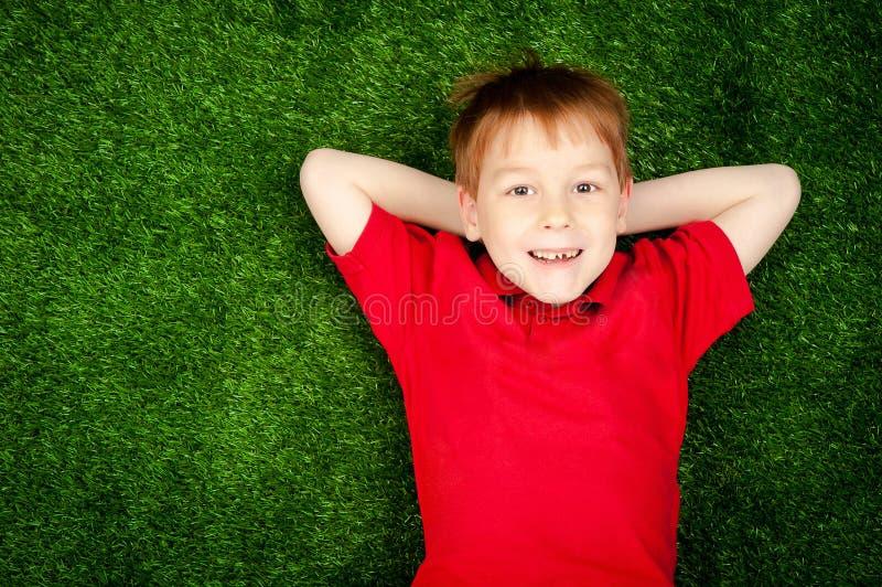 Menino que encontra-se em um gramado verde imagem de stock