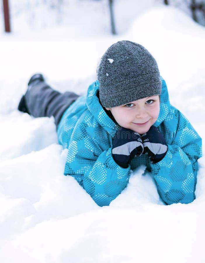 Menino que encontra-se em uma neve fotos de stock