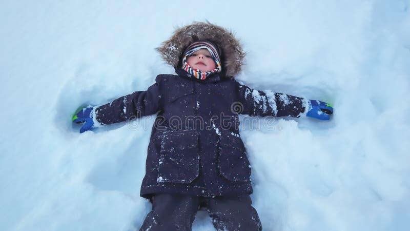 Menino que encontra-se em uma neve profunda fotos de stock royalty free