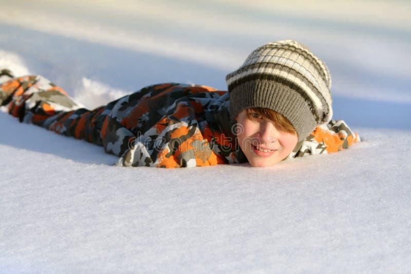 Menino que encontra-se na neve imagens de stock