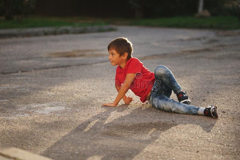 Menino que encontra-se no asfalto na rua imagens de stock