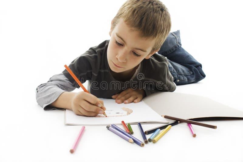 Menino que encontra-se no assoalho e que desenha no papel imagem de stock