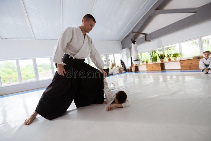 Menino que encontra-se no assoalho em seguida que tem a luta do aikido com seu instrutor imagem de stock