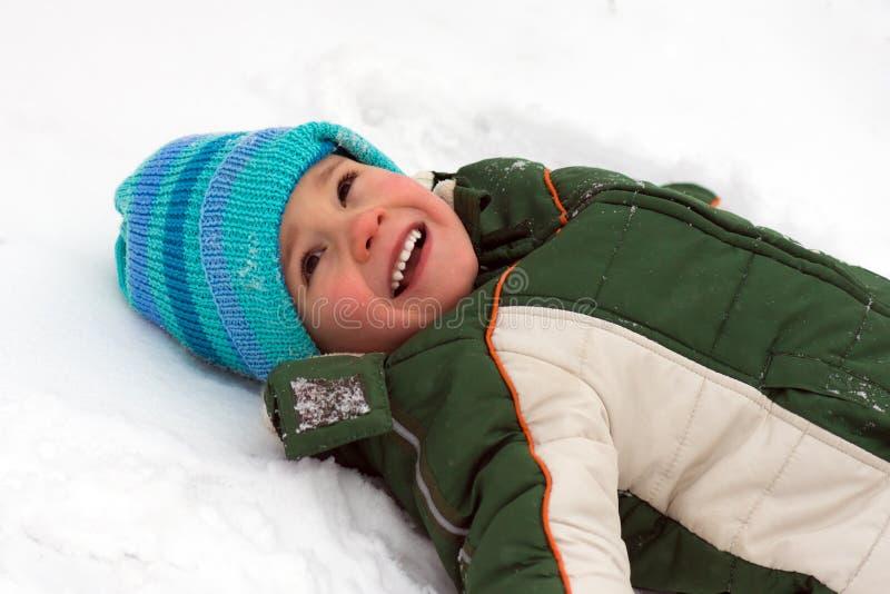 Menino que encontra-se para baixo na neve fotografia de stock