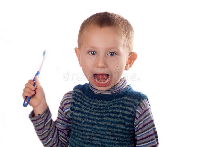 Menino que escova seus dentes após o banho imagem de stock royalty free