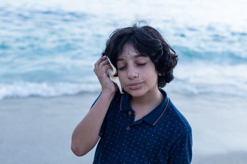 Menino que escuta o som da concha do mar imagens de stock royalty free