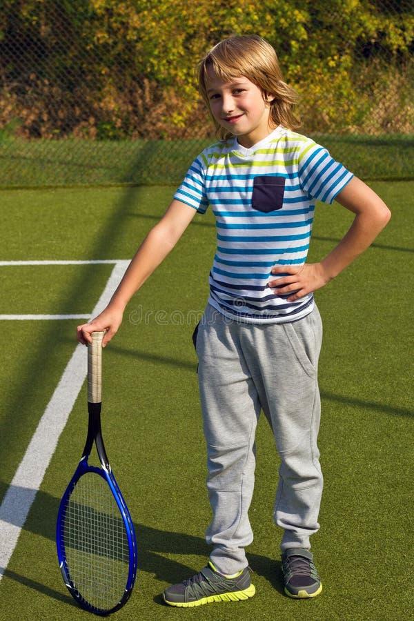 Menino que está com raquete e bola de tênis na corte no dia do sammer imagens de stock royalty free