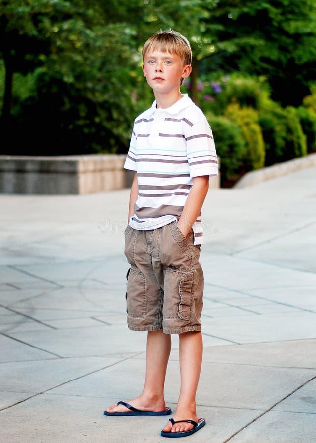 Menino que está Outisde no passeio - vertical foto de stock