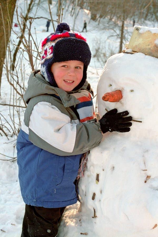 Menino que faz o boneco de neve imagens de stock
