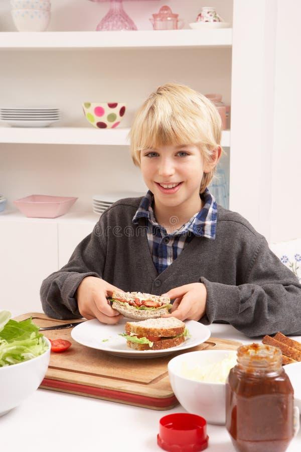 Menino que faz o sanduíche na cozinha imagem de stock royalty free