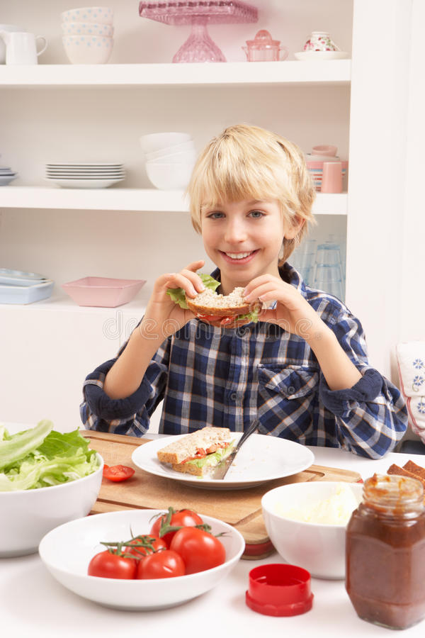Menino que faz o sanduíche na cozinha foto de stock