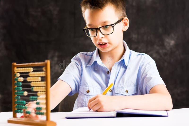 Menino que faz trabalhos de casa da matemática em casa foto de stock royalty free