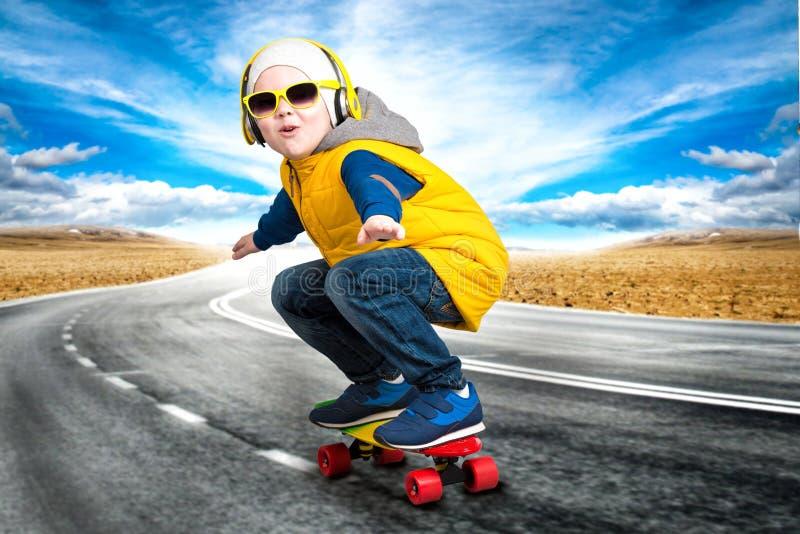 Menino que faz truques em um skate, patim na estrada O rapaz pequeno ao estilo do hip-hop fotografia de stock