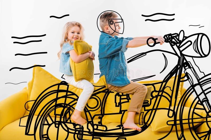 menino que finge ser um motociclista e um velomotor de montada ao sentar-se no sofá amarelo imagem de stock