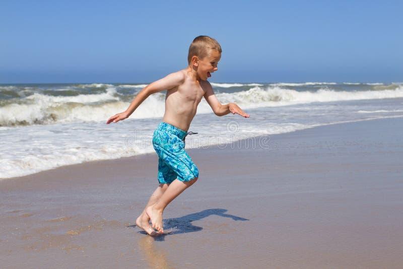 Menino que foge uma onda no Sandy Beach fotos de stock royalty free