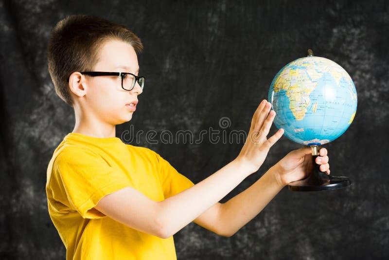 Menino que gira e que olha o globo foto de stock