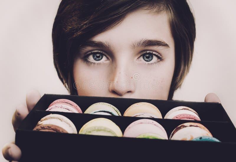 Menino que guarda macarons da sobremesa na caixa de madeira preta foto de stock royalty free