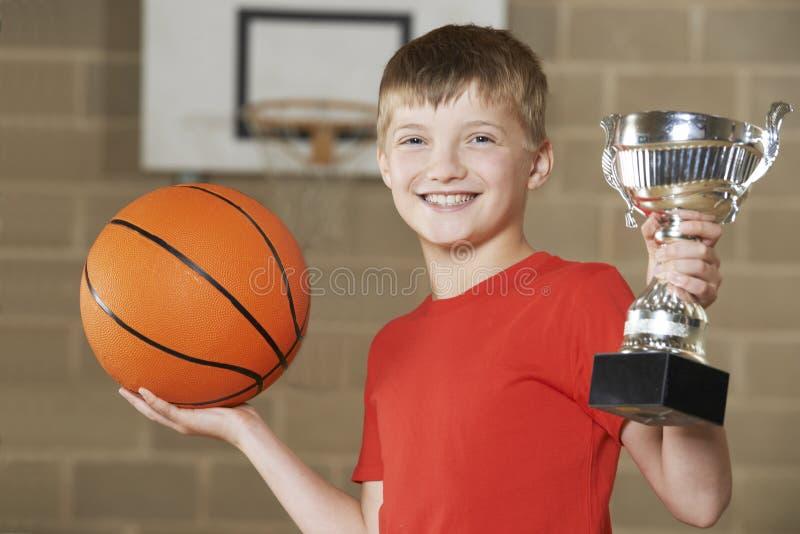 Menino que guarda o basquetebol e o troféu no ginásio da escola fotografia de stock