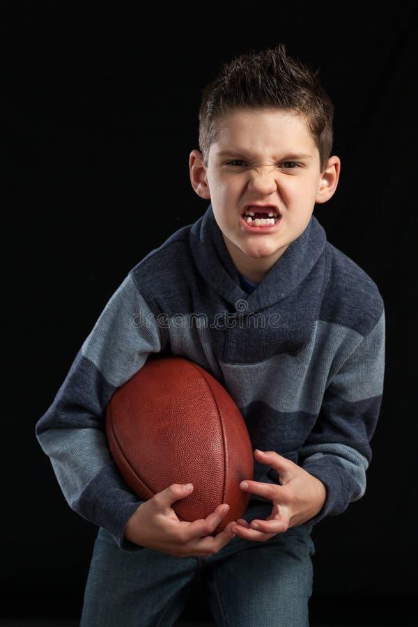 Menino que guarda os dentes faltantes do futebol imagens de stock