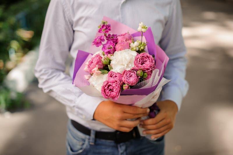 Menino que guarda um ramalhete pequeno das flores imagens de stock royalty free