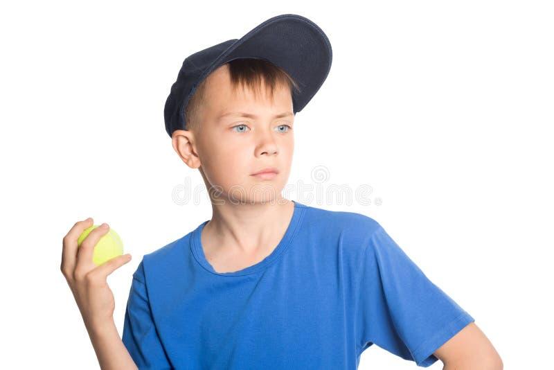 Menino que guarda uma bola de tênis foto de stock royalty free