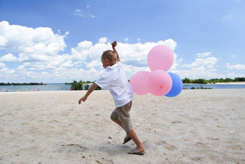Menino que joga com balões imagens de stock royalty free